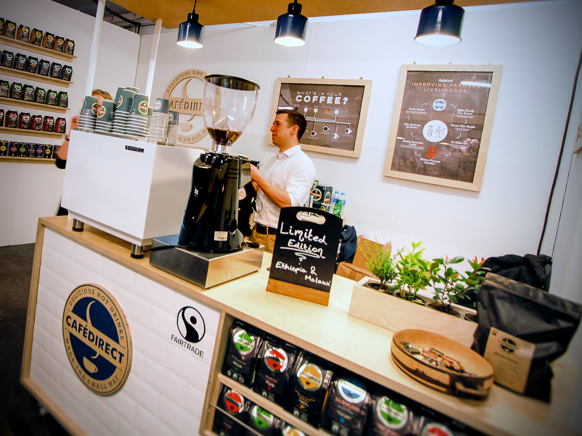 Liqui Exhibition Stand Design - Cafedirect trade stand showing a bespoke counter with built in display shelving and overhead Cell Lights.