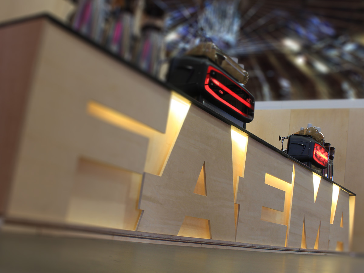 Liqui Exhibition Stand Design - Faema trade stand at Amsterdam Coffee Festival showing front of counter with back-lit, cut-out birch ply logo.