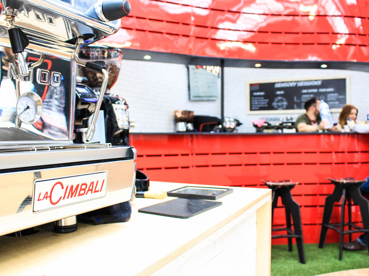 Liqui Exhibition Stand Design - La Cimbali trade stand at London Coffee Festival showing black Splice bar stools at red counter with coffee machine in foreground