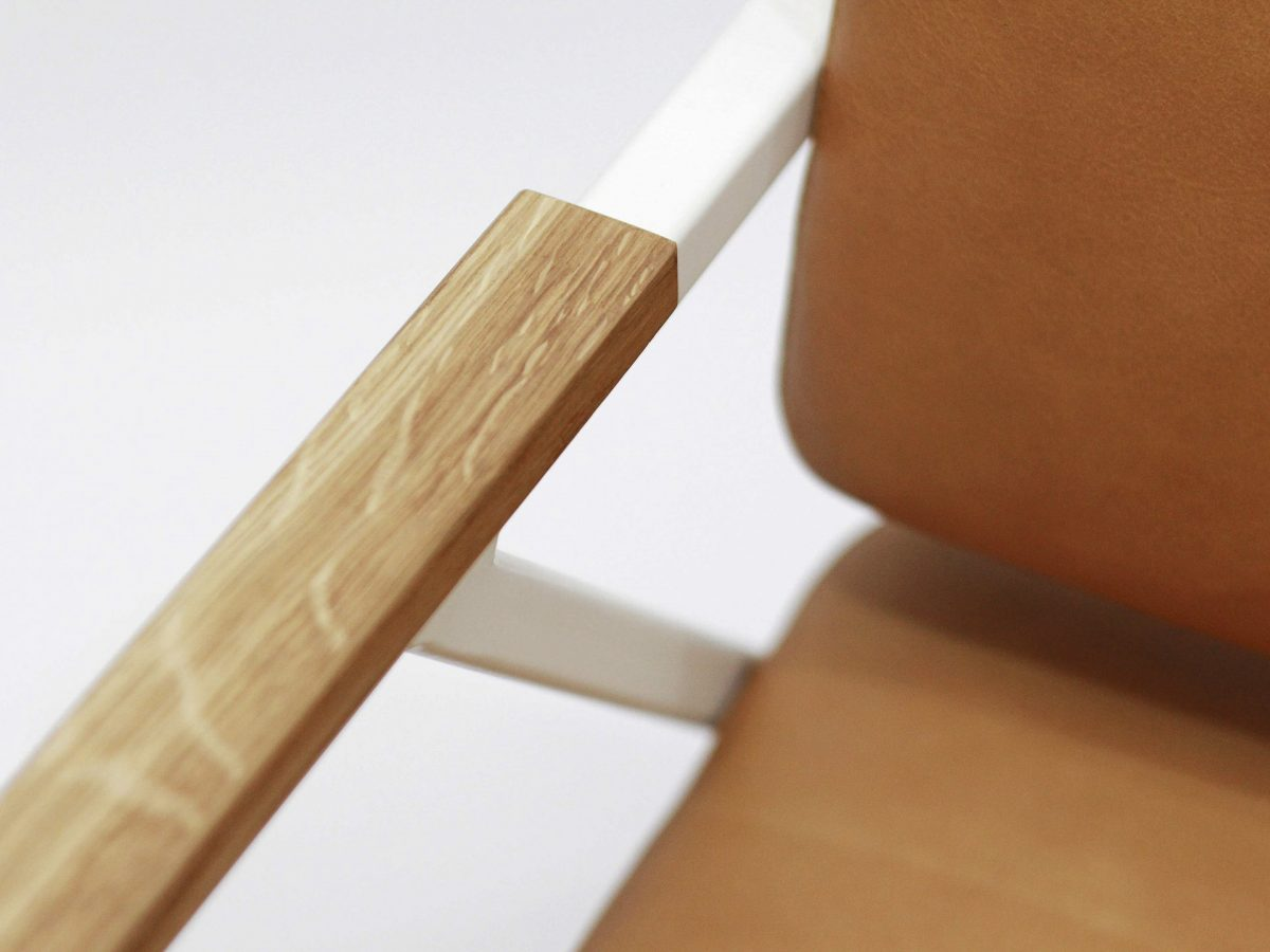 Liqui Studio Commercial Easy Chair - Close up of arm finished in solid oak on the steel frame powder coated in white with leather upholstered seat and back rest.