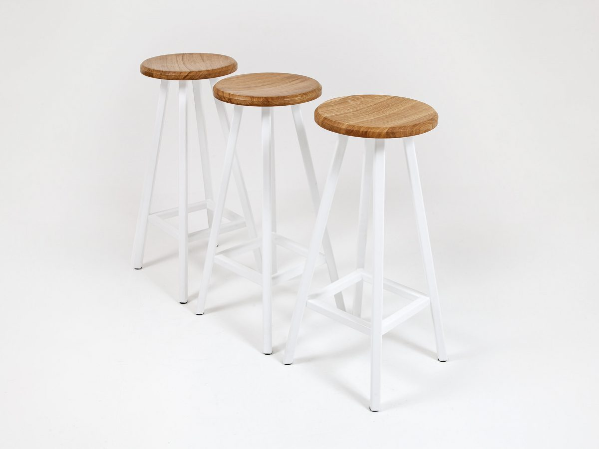 Liqui Commercial Studio Bar Stool - View of three stools showing powder coated stainless steel legs in white with concave shaped seat in sustainably sourced oak.