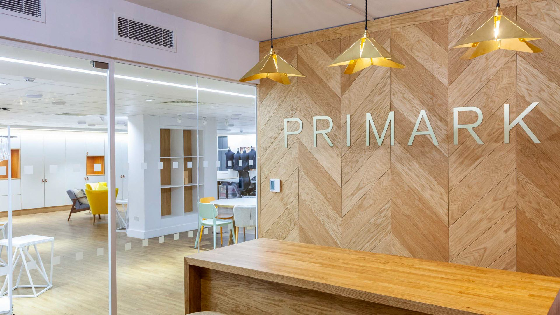 Reception area for Primark office design showing three splice pendant lights by interior designers, Liqui Group